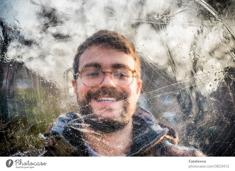 Porträt eines lächelnden jungen Mannes hinter Eis Junger Mann Bart Brille brünett Person männlich Winter gefroren kalt Braun Grün Tag Tageslicht