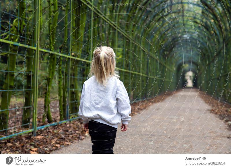 kleines süßes blondes Kind geht allein in einer Tunnelstraße in einem Park, schöner grüner Wald mit grauer Kapuze wenig Spaziergang niedlich Kindheit jung