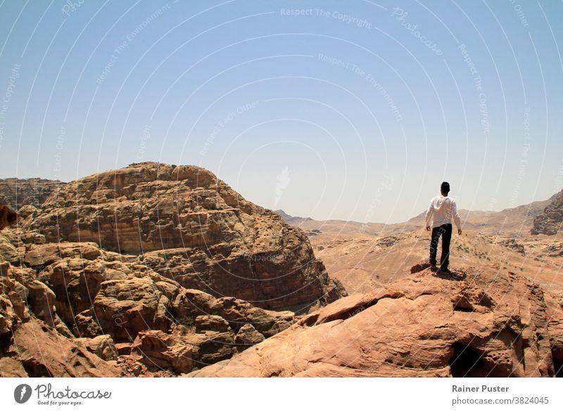 Junger Mann auf dem Gipfel eines Gipfels mit Blick über ein Tal in der rauen Landschaft von Petra, Jordanien Abenteuer Textfreiraum wüst die Welt erkunden