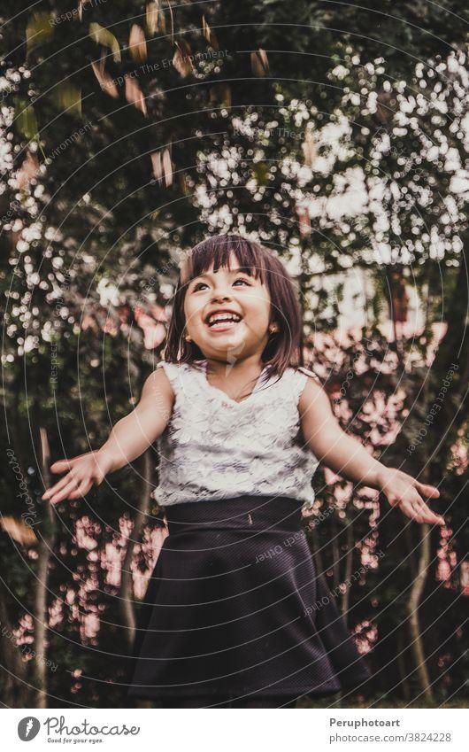 Kleines süßes kurzhaariges Mädchen wirft Blätter. Herbst Menschen Glück Kind fallen Park heiter Wald golden wenig Natur außerhalb spielerisch gelb Lachen lustig