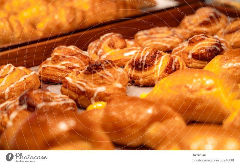 Bäckerei in braunem Holztablett in einer Bäckerei. Frisch gebackenes Gebäck. Auslage für süßes Brot auf der Theke. Kohlenhydrathaltiges Essen. Snack zum Frühstück oder Mittagessen. Bäckerei-Einzelhandelsgeschäft. Hausgemachte Bäckerei.