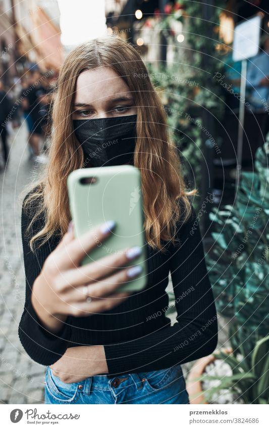 Junge Frau führt Videoanrufgespräche, während sie mit der Gesichtsmaske in der Innenstadt läuft, um eine Virusinfektion zu vermeiden Anruf Pflege Kaukasier