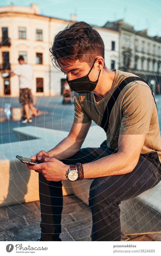 Junger Mann sitzt im Stadtzentrum, benutzt ein Smartphone und trägt die Gesichtsmaske, um eine Virusinfektion zu vermeiden Kaukasier Gespräch covid-19 Lifestyle
