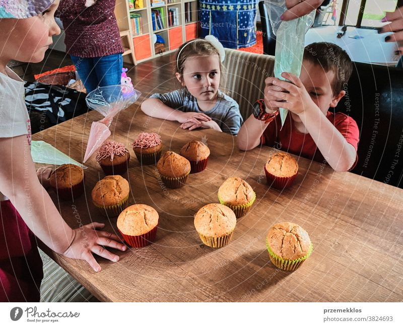 Kinder backen Muffins, bereiten Zutaten vor, dekorieren Kekse Cupcake dekorierend vorbereitend Essen zubereiten Familie heimisch Zusammensein Kindheit Glück