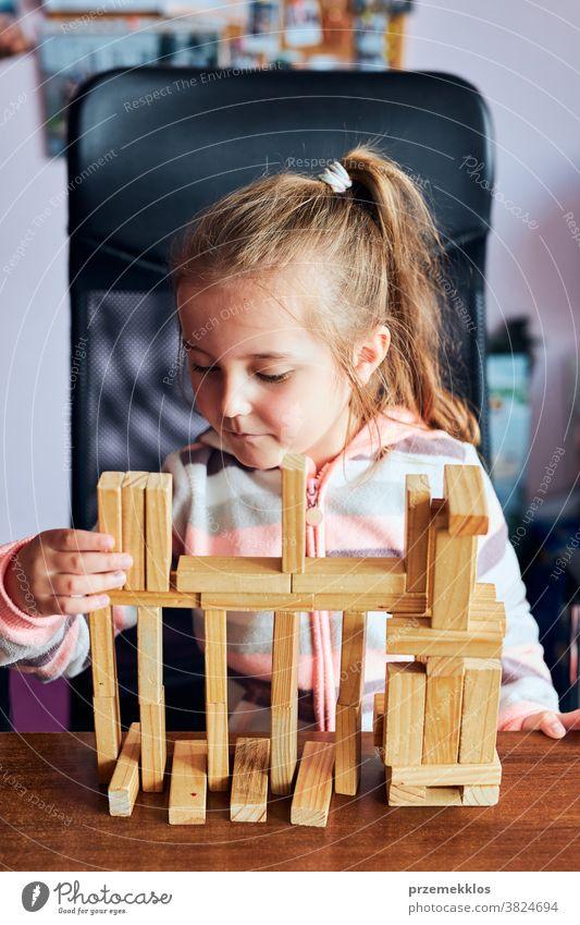 Kleines Mädchen im Vorschulalter spielt mit Holzklötzen Spielzeug, das ein Haus baut Aktivität Klotz Blöcke Baustein bauen Kind Kindheit Konzept Konstruktion