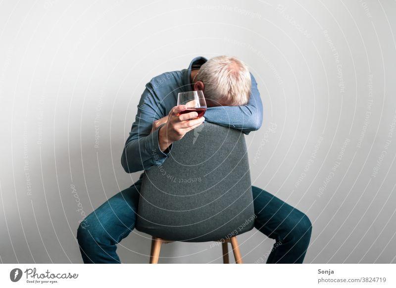 Depressiver Mann sitzt auf einem Sessel mit dem Kopf auf einem Arm und einem Glas Cognac in der Hand Depression Verzweiflung Einsamkeit traurig unglücklich