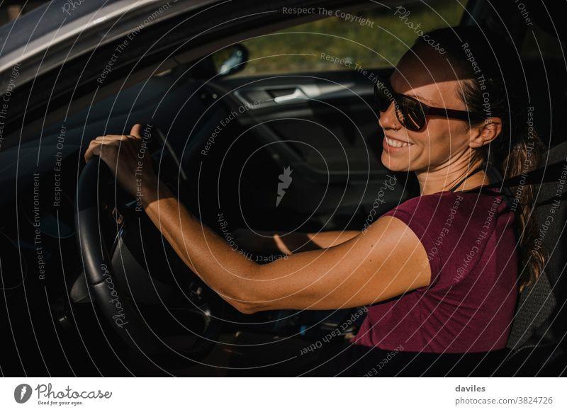 Frau in ihrem Auto hält das Lenkrad und lächelt. Laufwerk sorgenfrei Lachen Glück Lächeln Freude heiter junger Erwachsener Anschluss Autoreise echte Menschen