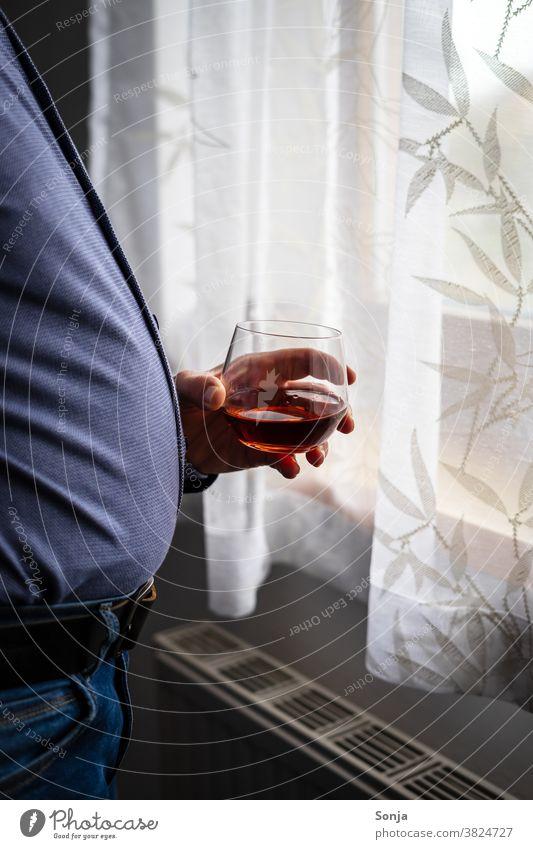 Übergewichtiger Mann mit einem Glas Cognac steht an einem Fenster Trinkglas Hand halten beobachten Einsamkeit zuhause zuhause bleiben dick Coronavirus