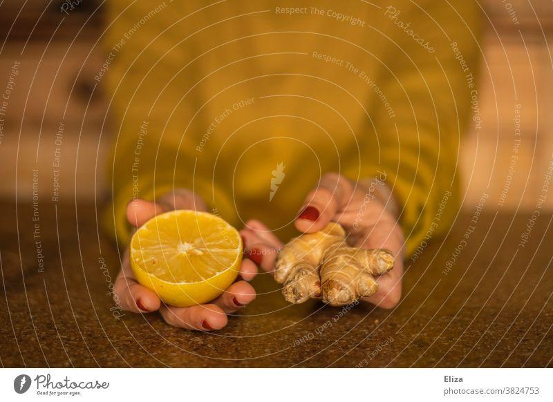 Immunsystem in der Erkältungszeit stärken: Frau hält eine halbe Zitrone und ein Stück Ingwer. immunsystem gesund Gesunde Ernährung Grippe vorbeugen Vitamin C
