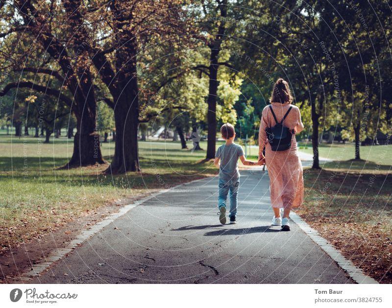 Hand in Hand Mutter mit Kind spaziert durch einen herbstlichen Park Stadt Spaziergang Spazierweg spazieren spazierengehen Mutter mit Sohn Junge Frau Liebe