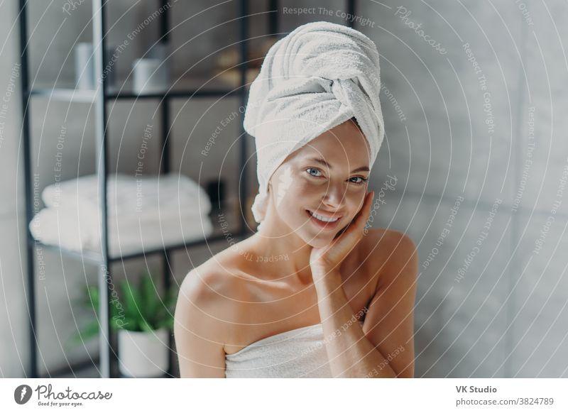 Schöne europäische Frau mit Make-up berührt die Haut, hat minimales Make-up, hat gesunde, strahlende Haut, in ein Badetuch gewickelt, genießt die Ruhe zu Hause. Spa-Frau posiert im Badezimmer. Schönheit, Wellness-Konzept
