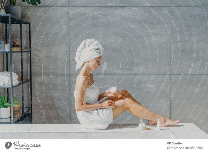 Horizontale Aufnahme einer entspannten jungen Europäerin trägt feuchtigkeitsspendende Körpercreme auf die Beine auf, in ein Badetuch gewickelt, hat ein zartes Lächeln, gesunde, erfrischte Haut nach dem Bad, posiert in einem gemütlichen Badezimmer.