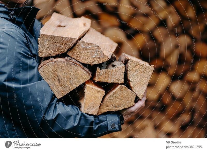 Unbekannter Mann trägt mit Jacke bekleidet einen Haufen Holz zum Feuermachen. Gesichtsloser Mann trägt Brennholz ins Haus hölzern männlich im Freien Totholz