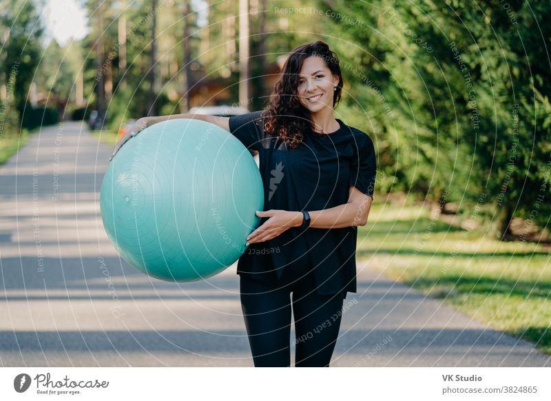 Außenaufnahme einer brünetten Frau posiert mit einem großen Fitball, in Sportkleidung gekleidet, trainiert unter freiem Himmel, geht auf der Straße, posiert in Waldnähe. Fitnesstrainerin geht in die Meisterklasse für schwangere Frauen