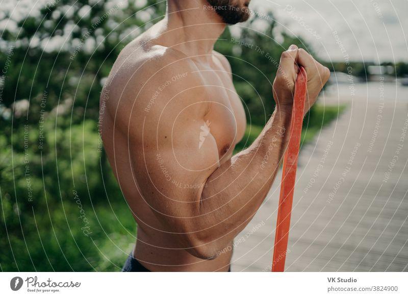 Cropped shot eines nicht erkennbaren muskulösen Mannes hat Training Bizeps Übung steht im Profil zeigt starke Muskeln, verwendet Widerstandsband, strebt nach starkem Körper. Bodybuilding, Motivationskonzept