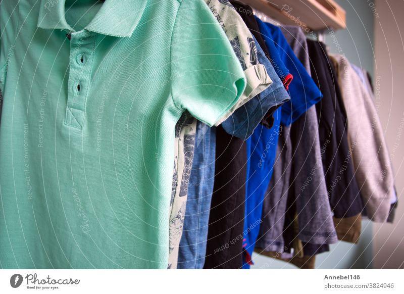 Jungen ziehen Kleider an, die in einem Metallregal hängen, Kinderzimmer der Jungen Lagerung im Zimmer Mode Ablage Bekleidung Kleidung anhaben Kleiderschrank
