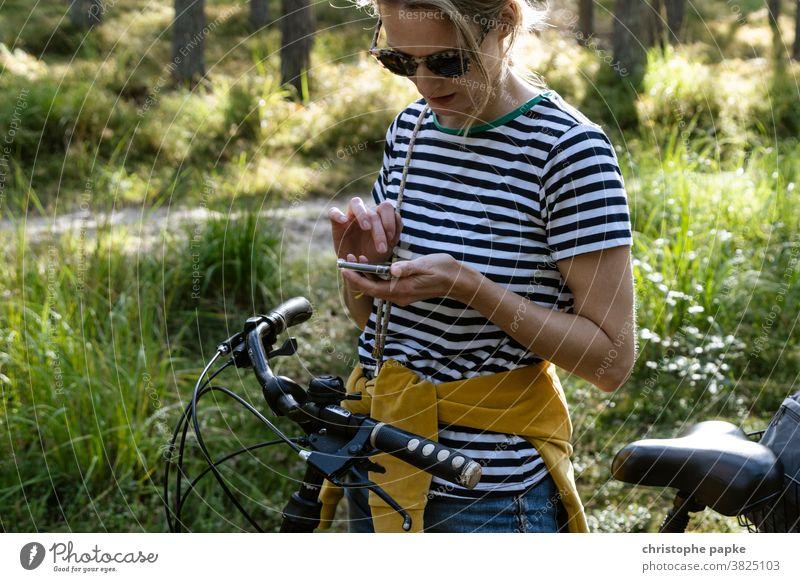 Frau mit Fahrrad sucht Weg auf Smartphone Fahrradfahren Navigation suchen Wald Fahrradtour Handy Freizeit & Hobby Tag Außenaufnahme Farbfoto Ausflug Natur