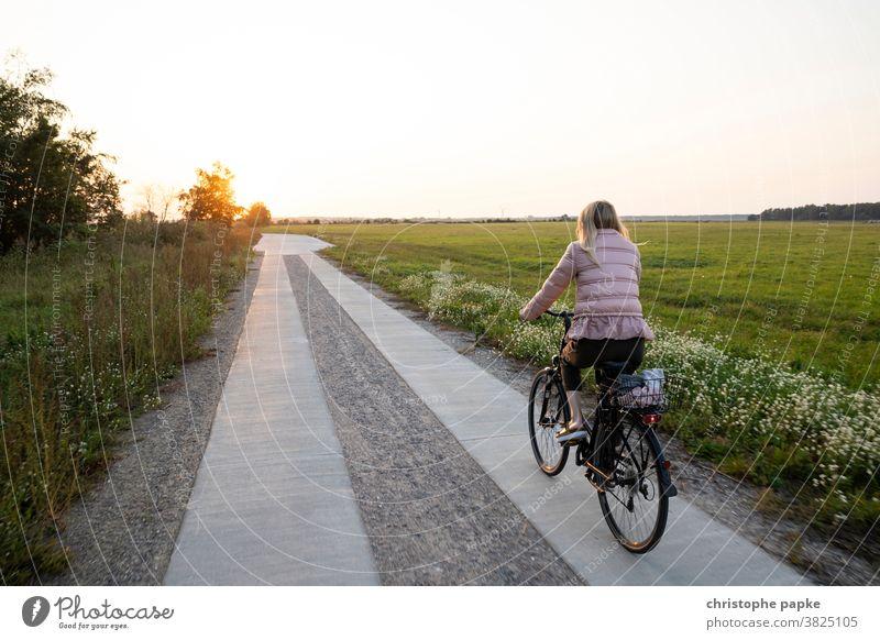 Frau fährt Fahrrad im Sonnenuntergang Fahrradfahren Feld Fahrradtour Wege & Pfade Bewegung Mobilität Ausflug Freizeit & Hobby blond Außenaufnahme Farbfoto