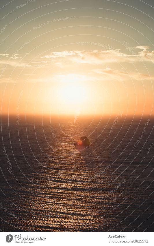 Ein gewaltiger Sonnenuntergang über einem einsamen Felsen mitten im Ozean Meereslandschaft beleuchtet im Freien Sonnenlicht Natur Sonnenaufgang