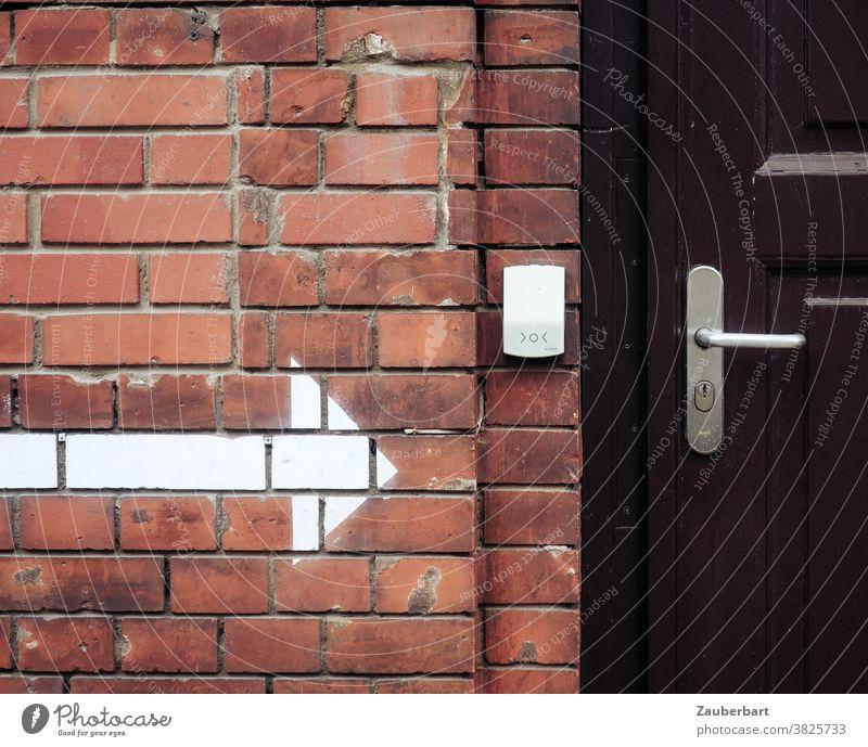 Ziegelwand, weißer Pfeil, Klingel und Holztür zeigen Wand Klinker ziegelrot Tür Türklinke Eingang Hinweis braun verschlossen Wegweiser Da lang Schloss