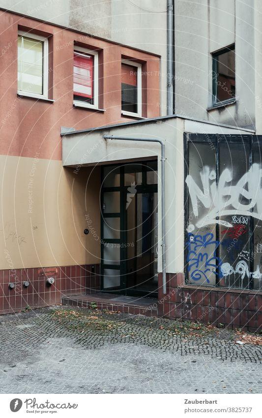 Hauseingang, Fenster und Graffiti in der Stadt Eingang Wohnhaus Eingangstür Großstadt trist Tristesse Realität Fassade Gebäude Tür Mauer Bauwerk Wand