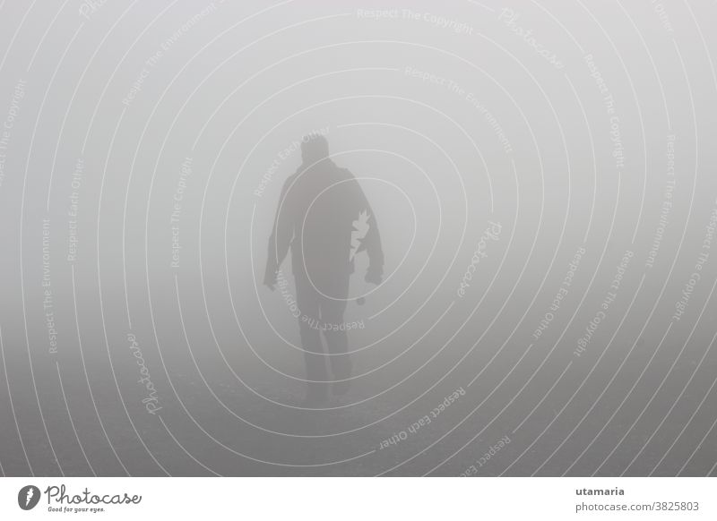 A man walks up a hill in dense fog. On a mountain footpath, height approx. 1300 m.  Hinterstoder, Upper Austria, Europe. surreal fantasy fading future uncertain