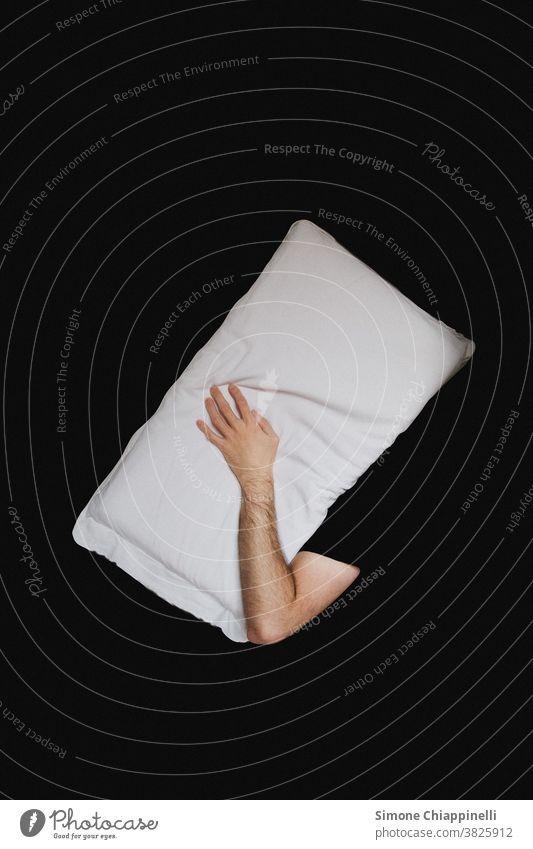 Schlafen mit Kissen auf dem Kopf auf schwarzem Hintergrund schwarzer Hintergrund Kopfkissen abstrakt konzeptionell Konzept weißes Kissen schlafen Bett träumen