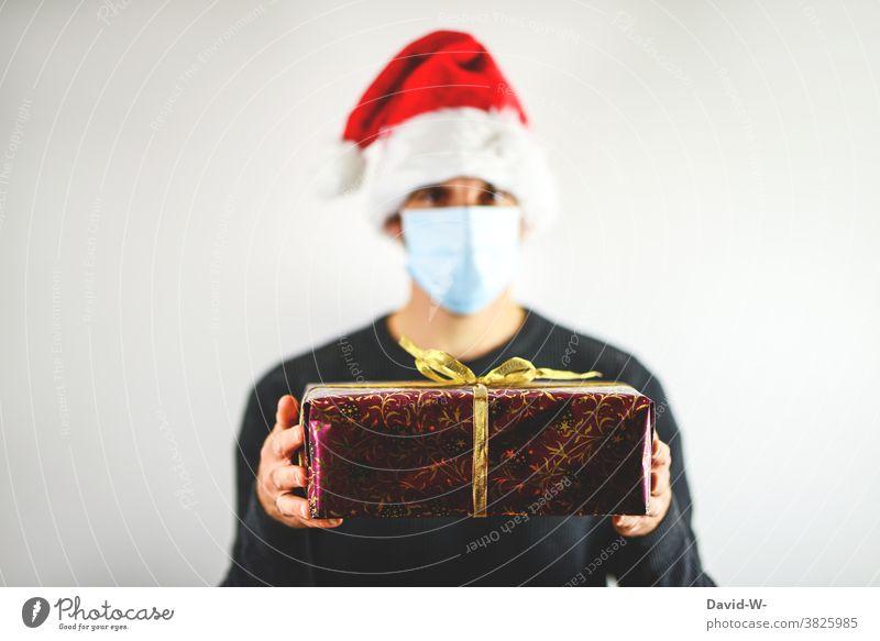 frohe Weihnachten - Mann hält unter Corona-Bedingungen Geschenk in den Händen Atemschutzmaske Mundschutz Nikolausmütze Bescherung pandemie Schutz Virus Schützen