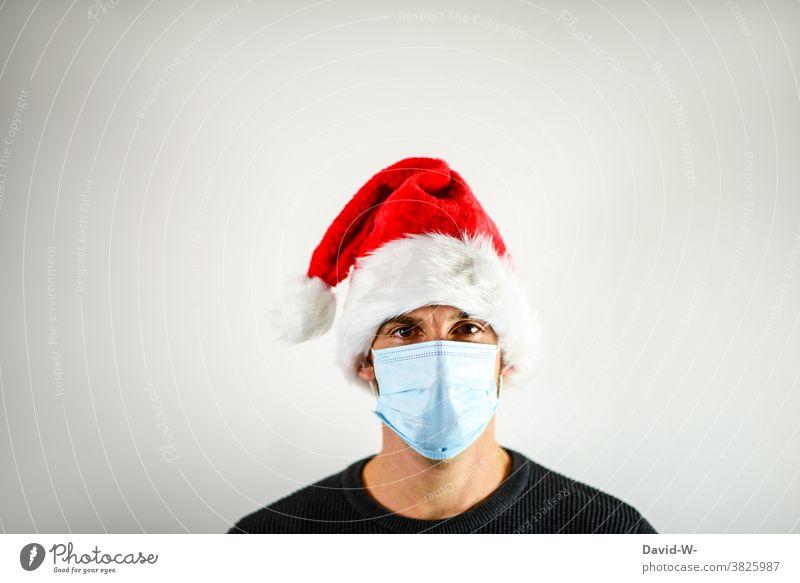 Corona und Weihnachten - Mann mit Atemschutzmaske und Nikolausmütze Mundschutz adventszeit Maske Pandemie Coronavirus Infektionsgefahr Schutz Gesundheit