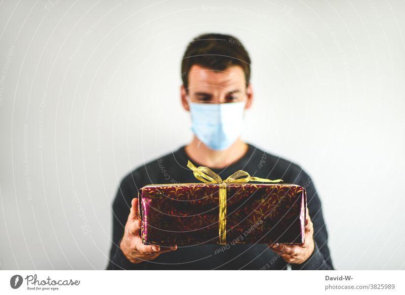 Corona und Weihachten - Mann mit Maske hält Geschenk in den Händen Weihnachten Atemschutzmaske Mundschutz abstand Pandemie schenken