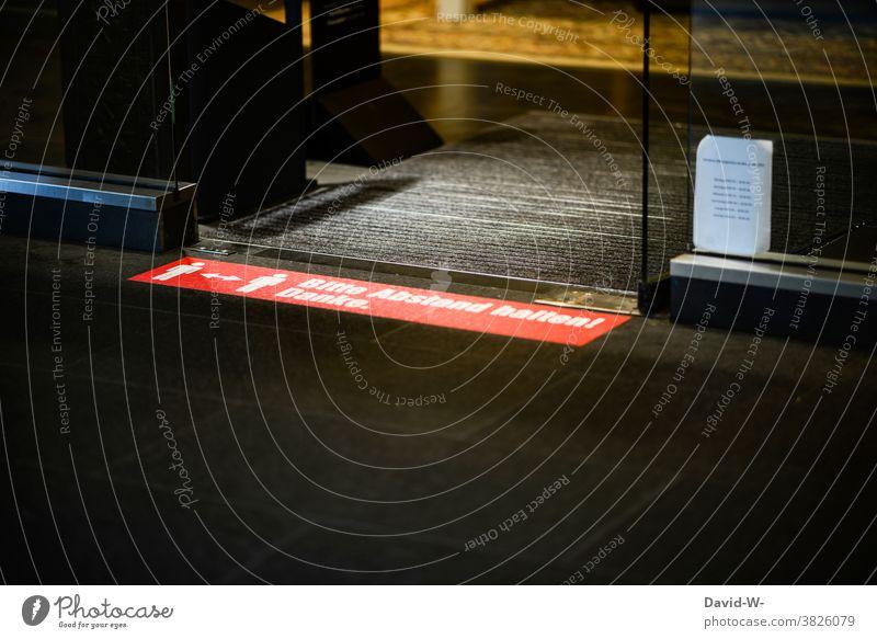 Corona - Bitte Abstand halten Hinweisschild abstand halten Schild Markierung Boden Geschäft Anordnung Sicherheit Infektionsgefahr Schutz Pandemie Pfeil