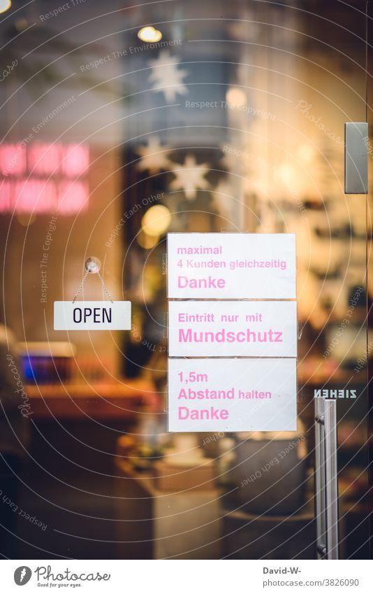 Corona - Hinweisschilder in einem Geschäft Schilder abstand halten Anweisungen mundschutzpflicht Mundschutz Weihnachten Prävention Gesundheit Einzelhandel