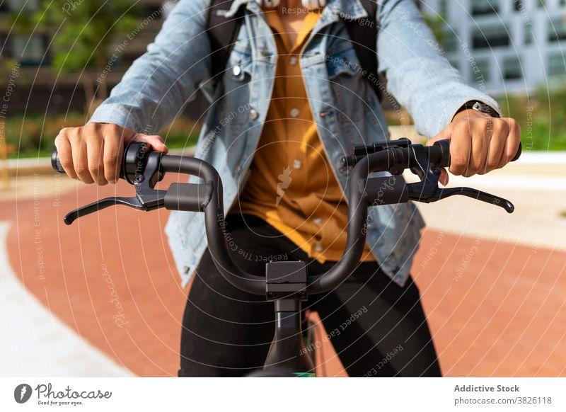 Crop Mann fahren moderne Fahrrad in der Stadt Mitfahrgelegenheit Straße Großstadt Verkehr Arbeitsweg männlich ethnisch Zeitgenosse Aktivität urban