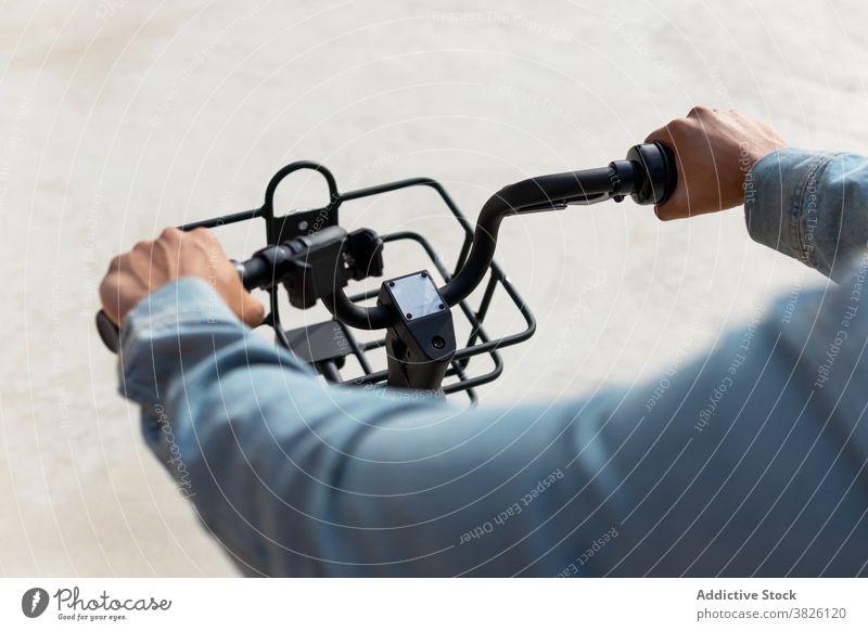 Crop Mann fahren moderne Fahrrad in der Stadt Mitfahrgelegenheit Straße Korb Großstadt Verkehr Arbeitsweg männlich ethnisch Zeitgenosse Aktivität urban