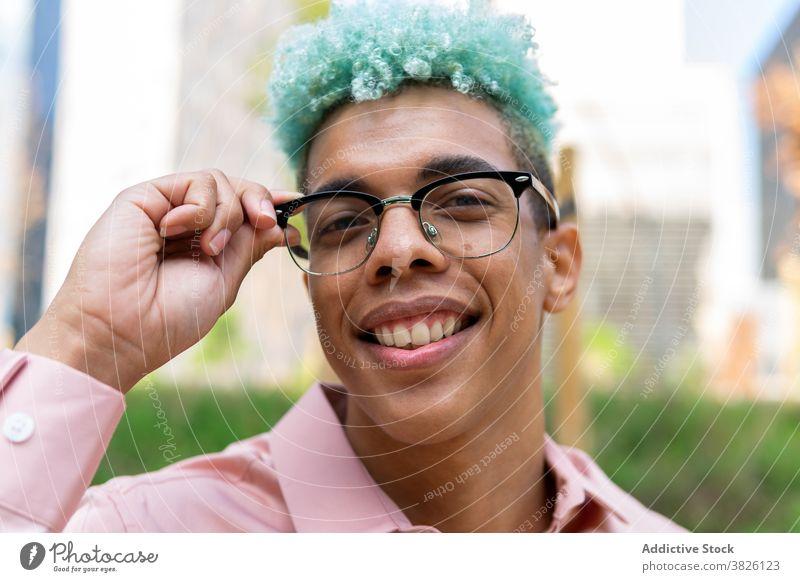 Lächelnde ethnischen Mann mit Afro-Frisur und in Gläser in der Stadt blaue Haare Afro-Look gutaussehend Stil Vorschein Brille trendy Generation männlich schwarz