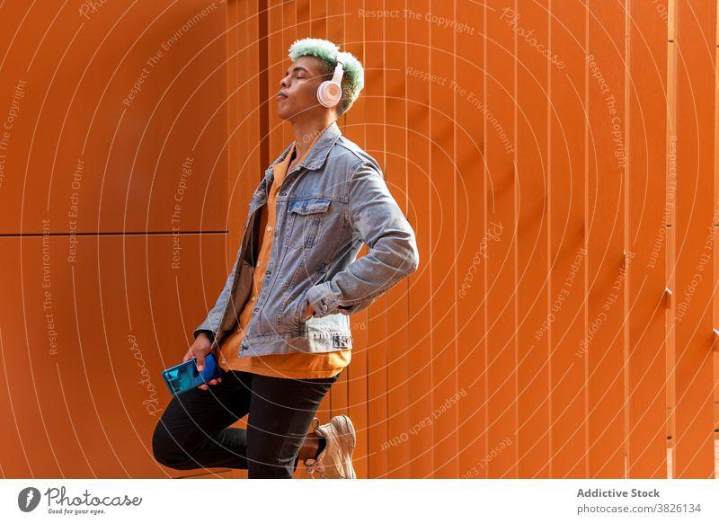 Verträumter ethnischer Mann beim Musikhören in der Stadt Kopfhörer Großstadt zuhören verträumt Hipster blaue Haare informell Gesang männlich schwarz
