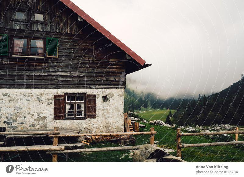 Berghütte Berge Wandern Bayern Hütte Haus Alm urig Holz Holzfenster Zaun Wiese Alpen Pause einkehren Wolken Nebel fensterläden alt heruntergekommen Wald