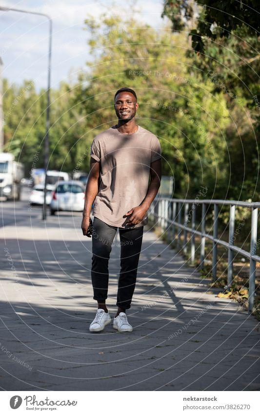 Junger schwarzer Mann geht auf dem Bürgersteig der Stadt Lächeln afrikanische ethnische Zugehörigkeit Spaziergang Straße echte Aufrichtigkeit reales Leben