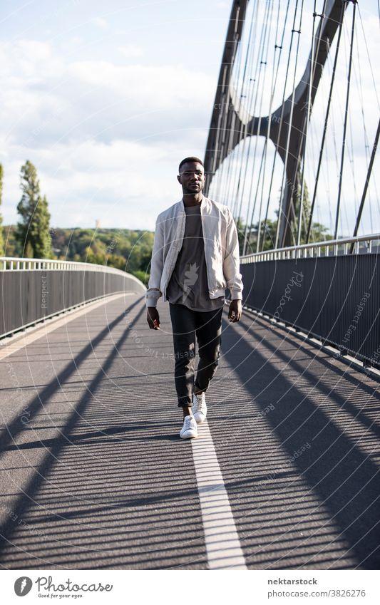 Junger schwarzer Mann geht selbstbewusst auf der Brücke afrikanische ethnische Zugehörigkeit Spaziergang echte Person eine Person Nur ein Mann modisch
