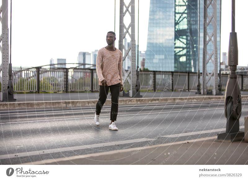 Mann überquert Straße mit gedrehtem Kopf durchkreuzen laufen Überfahrt Pullover Wegsehen Kopf gedreht Vorderansicht afrikanische ethnische Zugehörigkeit