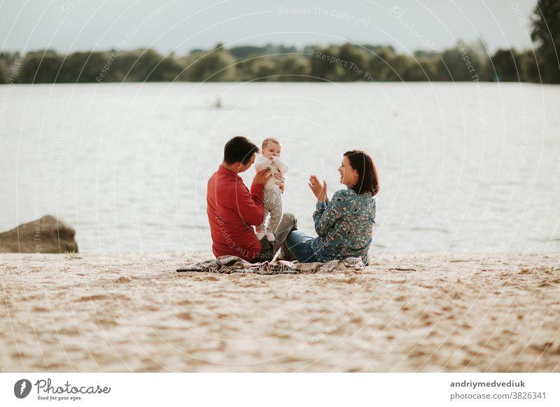 glückliche Familie, die sich am See ausruht. Familie mit einem kleinen Kind Natur Glück aussruhen Eltern Mutter Tochter Sommer Liebe Zusammensein Feiertag