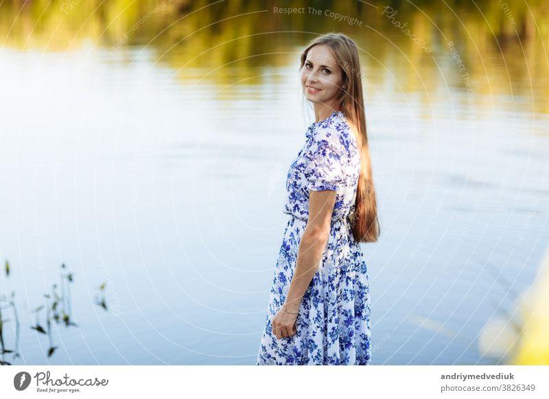 Schönes Porträt einer jungen Frau im Feld. Attraktives brünettes Mädchen mit langer lockiger Frisur in weißem Kleid träumend. Porträt eines schönen langhaarigen Mädchens