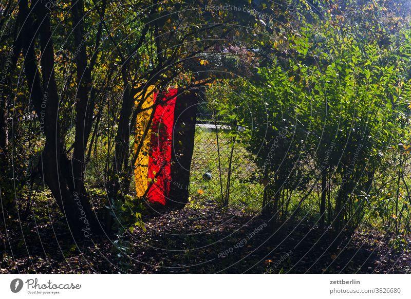 Deutschlandfahne in der Kleingartenkolonie deutschland deutschlandfahne gartenzaun grundstück herbst nationalismus patriotismus kleingarten kleingartenkolonie
