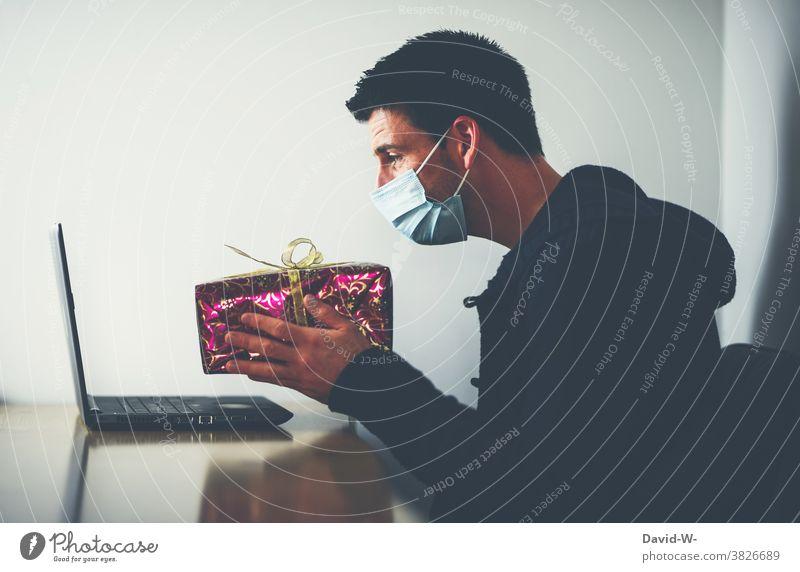 Corona und Weihnachten - Bescherung online - Mann sitzt mit Atemschutzmaske / Mundschutz am Laptop und hält ein Geschenk in die Webcam Quarantäne Pandemie
