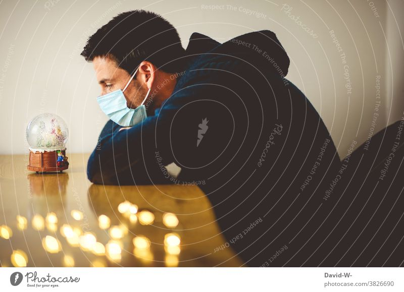 Weihnachten und Corona - Mann mit Atemschutzmaske schaut gedankenvoll in eine Schneekugel Weihnachten & Advent angst traurig einsam Mundschutz Quarantäne