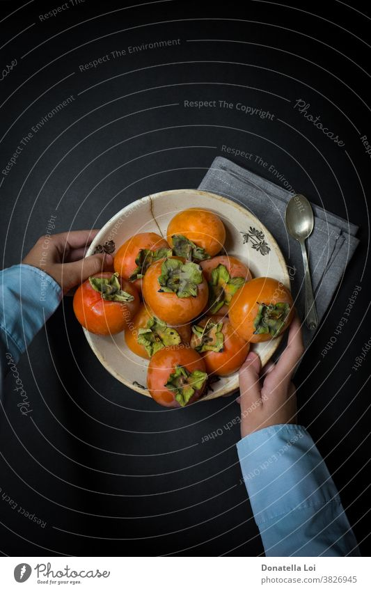 Teller Kakipflaume und Hände Herbst biologisches schwarzer Hintergrund Textfreiraum dunkel lecker Lebensmittel Früchte gut Gesundheit Beteiligung
