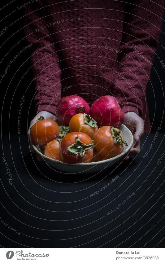Teller Kakipflaume und Granatäpfel Herbst biologisches schwarzer Hintergrund Textfreiraum dunkel lecker Lebensmittel Früchte gut Hände Gesundheit Beteiligung