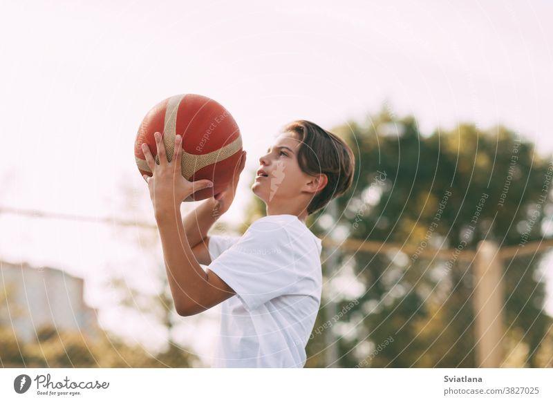 Nahaufnahme der Hände eines jungen Sportlers, der einen Basketball hält. Der Athlet bereitet sich auf den Wurf vor. Sport, Athlet Werfen Ball Spieler Junge