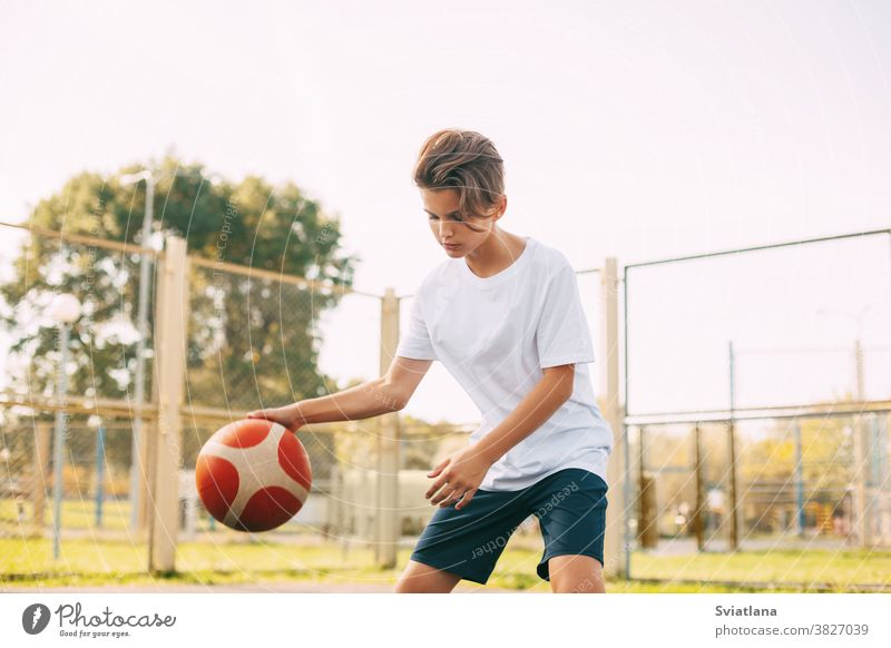 Ein fokussierter, süßer Athlet führt den Ball in einem Basketballspiel an. Ein Junge spielt nach der Schule Basketball. Sport, gesunde Lebensweise, Freizeit