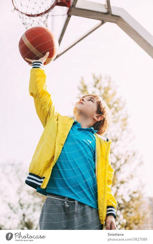Porträt eines süßen Basketball-Spielers, der mit einem Ball in der Hand neben dem Basketballkorb steht. Das Konzept des Sports und eines gesunden Lebensstils